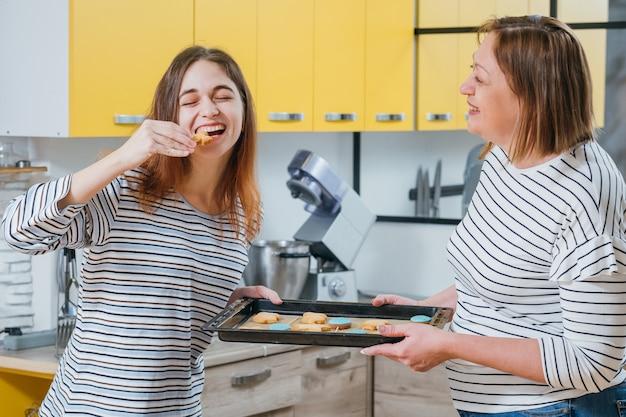과자 요리 취미. 어머니와 딸이 부엌에서 재미 수제 비스킷을 시도합니다.