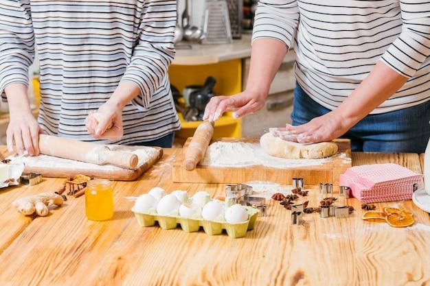 패스트리 요리 마스터 클래스. 반죽을 반죽하고 롤하는 방법을 가르치는 여자.