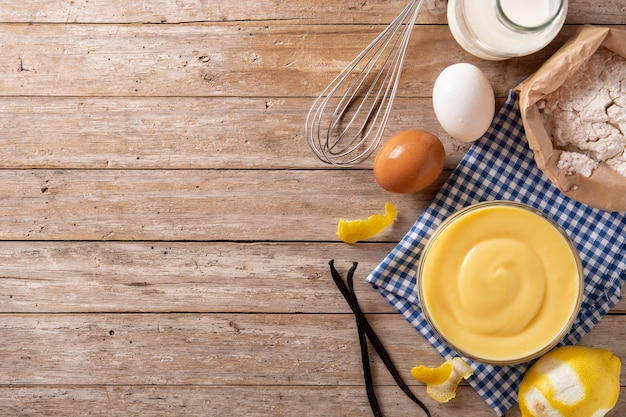 ボウルのペストリークリームと木製のテーブルの材料