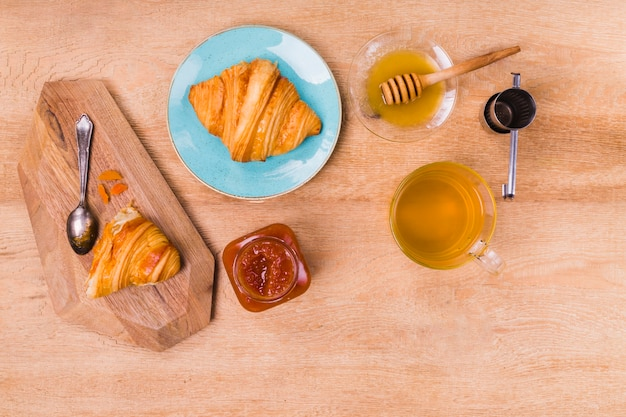 Pastry croissant with honey flat lay