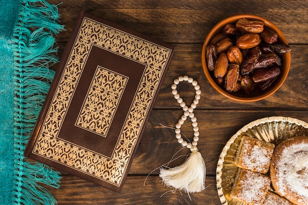 Pastry and dates near quran and beads