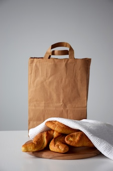 Pastry delivery of fresh bakery products, rolls under white kitchen napkin on white table and paper packaging