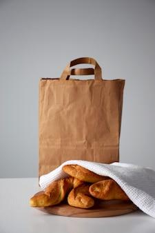 신선한 빵집 제품의 과자 배달, 흰색 테이블 및 종이 포장에 흰색 주방 냅킨 아래 롤