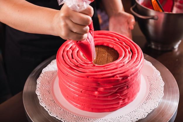 クリームの袖でケーキを飾るペストリーの手。