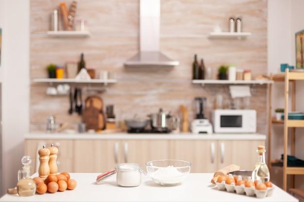 空のキッチンで自家製ケーキやパンのペストリーの材料。ガラスのボウルに小麦粉を入れ、テーブルに新鮮な卵を入れて調理する準備ができた調理器具を備えたモダンなダイニングルーム