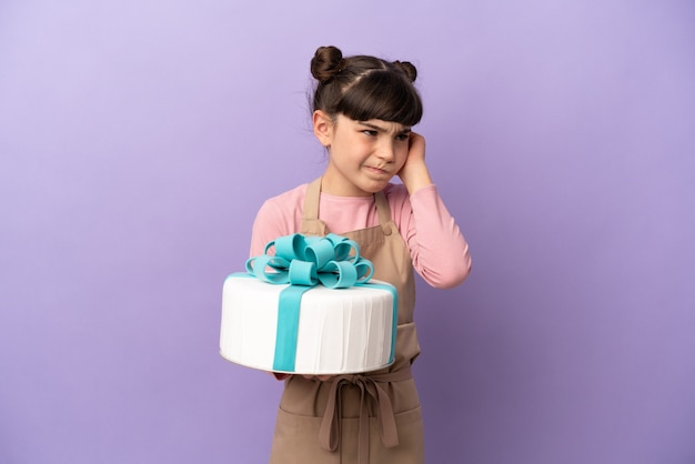 欲求不満と耳を覆う紫色の背景に分離された大きなケーキを保持しているペストリーの少女