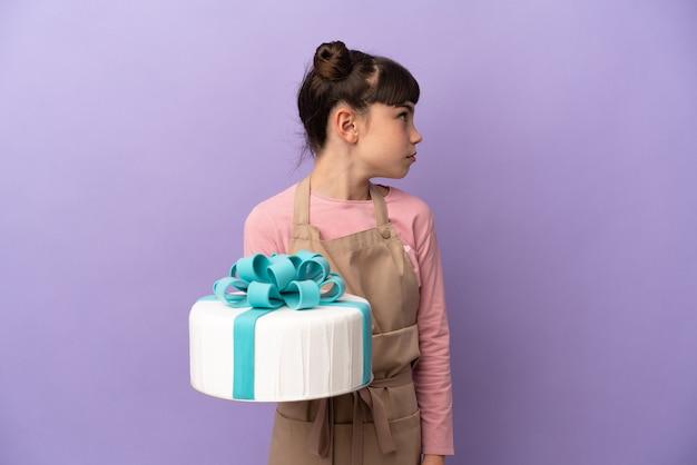 横を見て紫色の背景に分離された大きなケーキを保持しているペストリー少女
