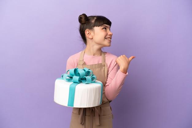製品を提示する側を指している紫色の背景に分離された大きなケーキを保持しているペストリーの少女