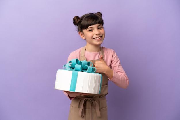 親指を立てるジェスチャーを与える紫色に分離された大きなケーキを保持しているペストリーの少女