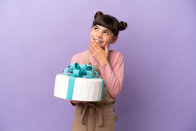 Маленькая девочка из кондитерских изделий, держащая большой торт, изолирована на фиолетовом, глядя вверх, улыбаясь
