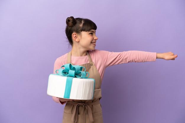 親指を立てるジェスチャーを与える紫色の壁に分離された大きなケーキを保持しているペストリーの少女