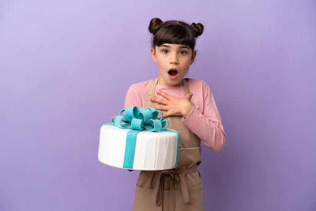 紫色の壁に隔離された大きなケーキを持っているペストリーの少女は、右を見ながら驚いてショックを受けました