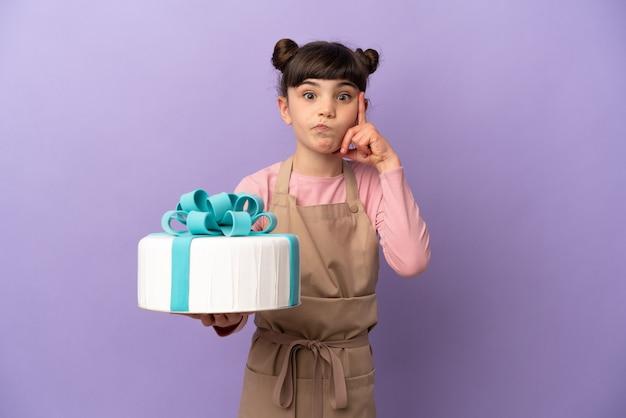 아이디어를 생각하는 보라색 벽에 고립 된 큰 케이크를 들고 과자 어린 소녀