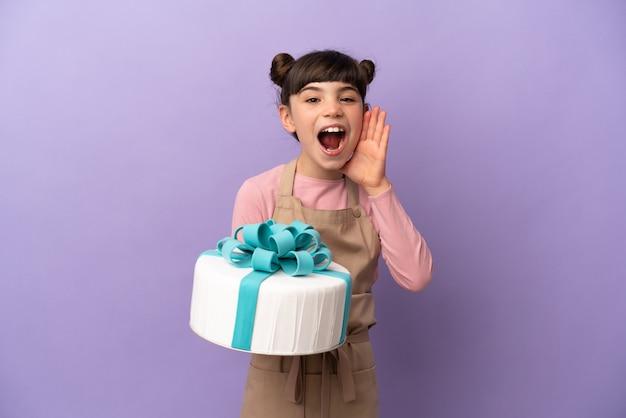 Маленькая девочка из кондитерских изделий держит большой торт на фиолетовой стене с удивлением и шокированным выражением лица