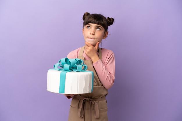孤立した大きなケーキを保持しているペストリー少女