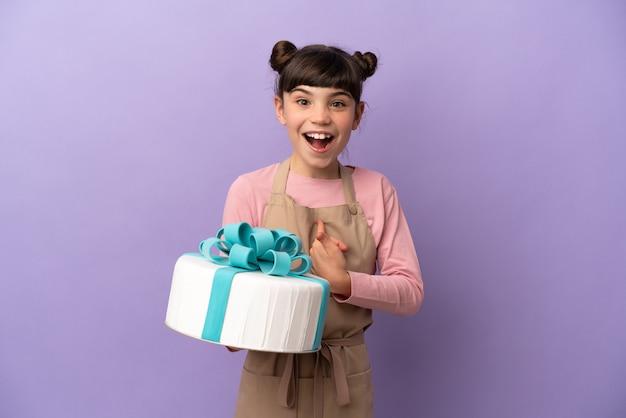 分離された大きなケーキを保持しているペストリーの少女