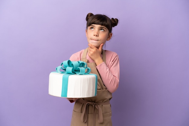 Pastry little girl holding a big cake isolated