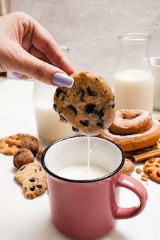 우유와 스콘을 곁들인 생과자 유기농 아침 식사를 닫습니다. 흰색 테이블에 머무르는 락토 음료 컵에 wholegrain 쿠키를 담그는 여자