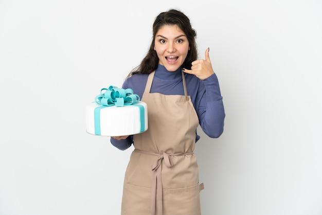Кондитерские изделия русский шеф-повар держит большой торт, изолированные на белом фоне, делая телефонный жест. перезвони мне знак