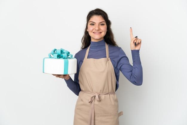 Русский шеф-кондитер держит большой торт на белом фоне, указывая вверх отличную идею