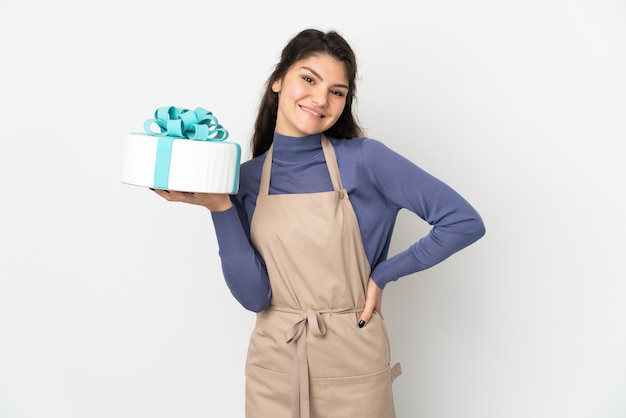 엉덩이에 팔을 포즈와 미소 흰색 배경에 고립 된 큰 케이크를 들고 과자 러시아 요리사
