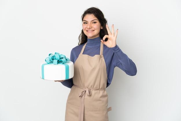 손가락으로 확인 표시를 보여주는 흰색 배경에 고립 된 큰 케이크를 들고 과자 러시아 요리사