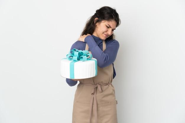 Русский шеф-кондитер держит большой торт на белом фоне и страдает от боли в плече за то, что приложил усилие