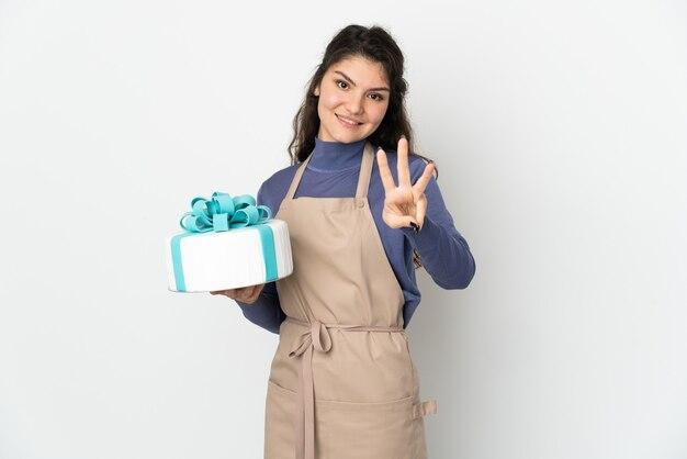 흰 벽에 행복하고 손가락으로 세 세에 고립 된 큰 케이크를 들고 과자 러시아 요리사