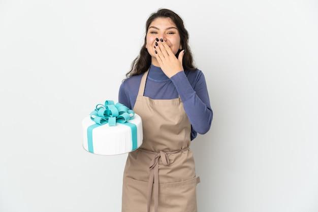 白い壁に分離された大きなケーキを持って幸せで笑顔の手で口を覆うペストリーロシア人シェフ