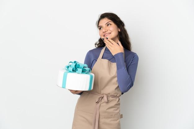 Русский шеф-кондитер держит большой торт на белой стене, глядя вверх, улыбаясь