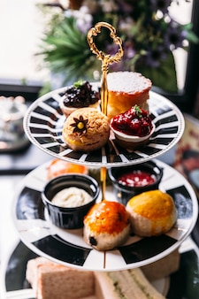 Pastry set for afternoon tea with scones, sandwiches and mini pies on marble top table.