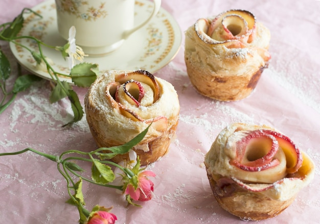 Pastry strudel in rose shape and floral decoration on pink background