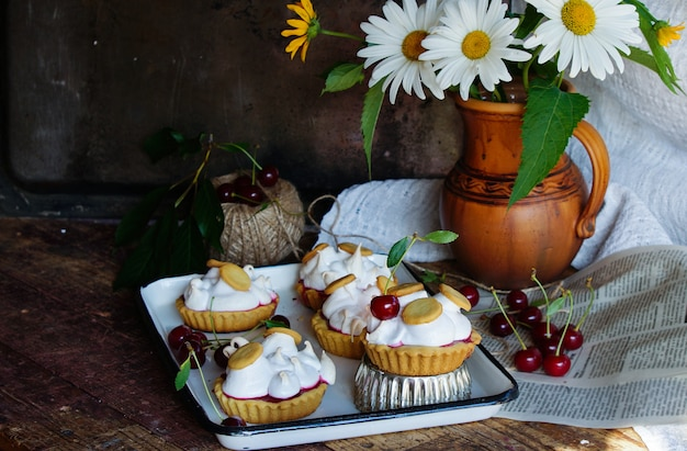 Pastry tartlets with meringue and cherry