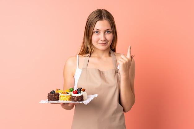 人差し指で指しているピンクのスペースに分離されたマフィンを保持しているペストリーウクライナシェフ素晴らしいアイデア