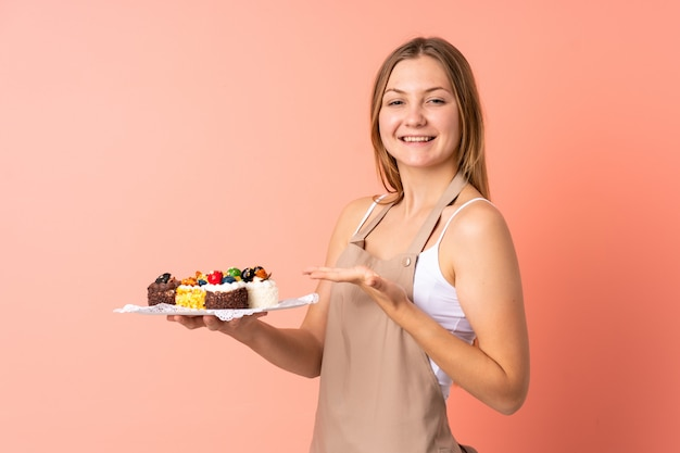 Pastry ukrainian chef holding a muffins isolated on pink space extending hands to the side for inviting to come