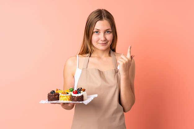 Pastry ukrainian chef holding a muffins isolated on pink space pointing with the index finger a great idea