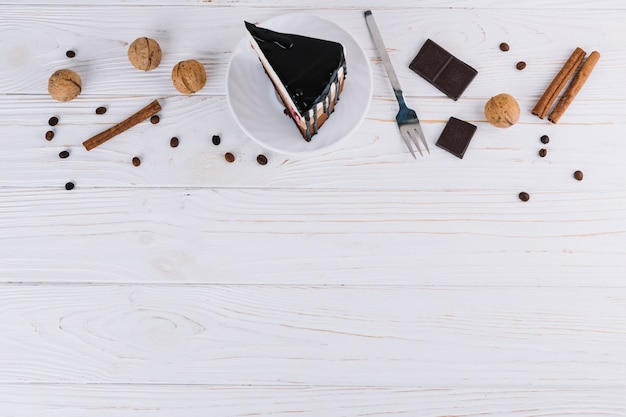 Pastry; walnuts; cinnamon; coffee beans; fork and chocolate bar over white wooden backdrop