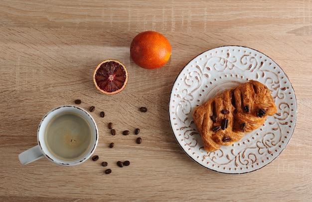 一杯のコーヒーとプレートにペカンナッツのペストリー