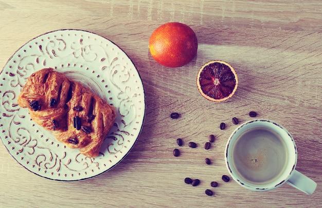 一杯のコーヒーと皿の上のペカンナッツのペストリー