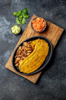 Patacon or toston, fried and flattened whole green plantain banana on white plate with tomato sauce and chicharron