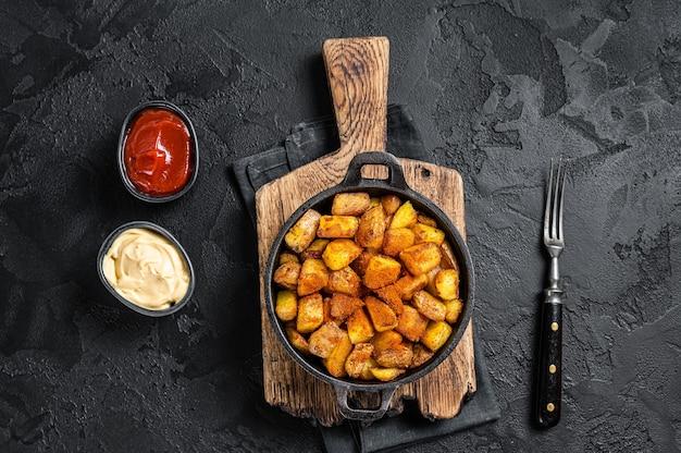 Patatas bravas, 매운 감자, 튀긴 감자와 매운 마늘 소스를 곁들인 스페인 요리. 검은 배경. 평면도.
