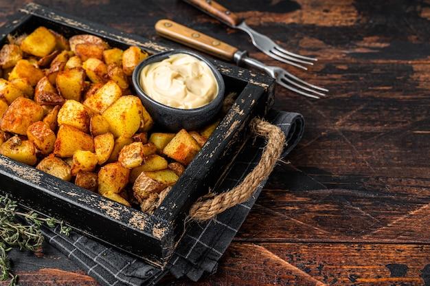 Patatas bravas 전통적인 스페인 감자 스낵 타파스. 어두운 나무 배경입니다. 평면도. 공간을 복사합니다.