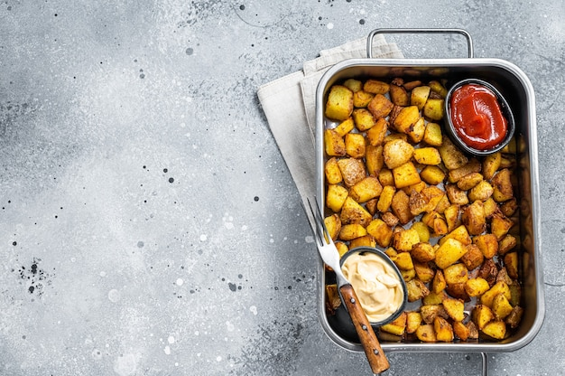 Patatas bravas 전통적인 스페인 감자 스낵 타파스는 강철 쟁반에 있습니다. 회색 배경입니다. 평면도. 공간을 복사합니다.