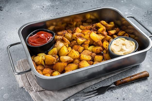 Patatas bravas 전통적인 스페인 감자 스낵 타파스는 강철 쟁반에 있습니다. 회색 배경입니다. 평면도.