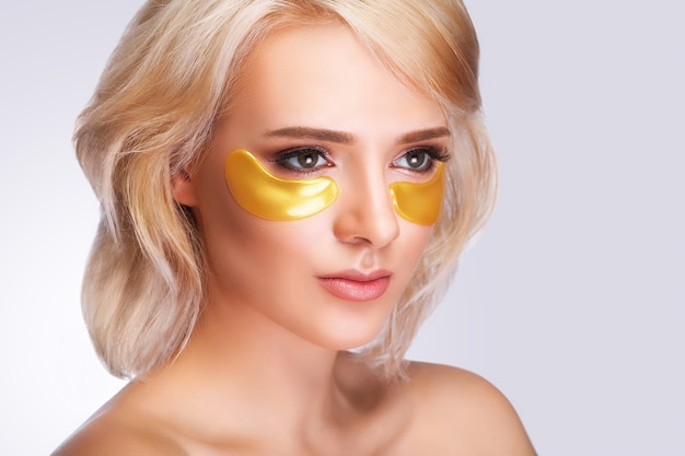Patch under eyes. beautiful woman face with gold hydrogel patches, lifting anti-wrinkle collagen mask on fresh healthy facial skin.