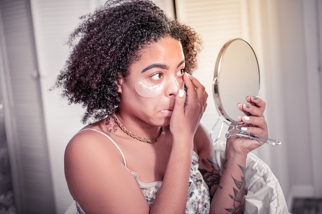 눈 아래 패치. 거울을보고 얼굴에 패치를 갖는 동안 눈 렌즈를 착용하는 집중된 단발 여성