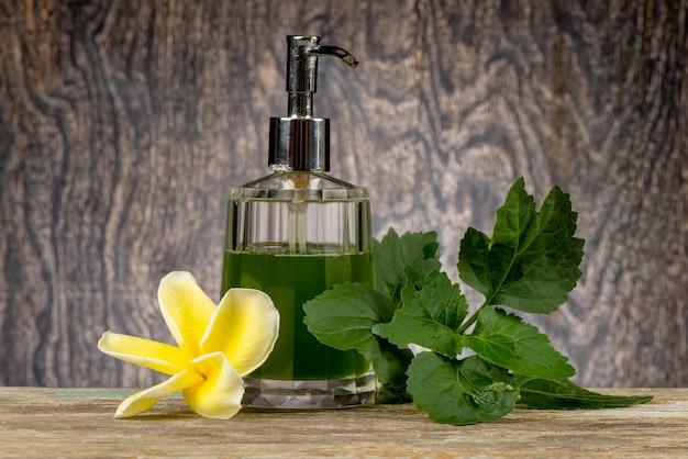パチョリの緑の葉と古い木の背景のボトルで抽出。