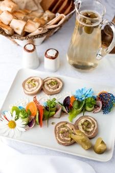 Паштет украшен огурцами и морковью и кувшин с компотом