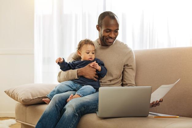 아버지 휴가. 노트북에서 작업하고 종이 한 장을 들고 웃고 그의 무릎에 그의 아들을 들고 명랑 검은 눈 수염 아프리카 계 미국인 남자