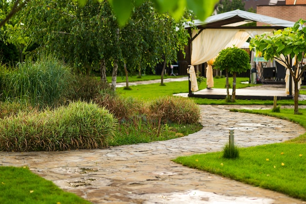 Path made of natural stone among trees in landscaping